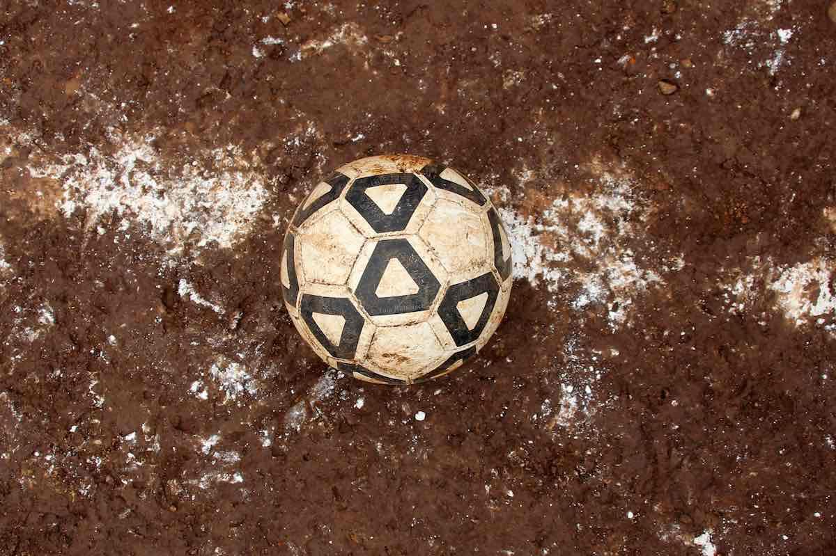 Ein Lederball liegt auf dem roten Hartplatz auf der Mittellinie.© Tom Rübenach