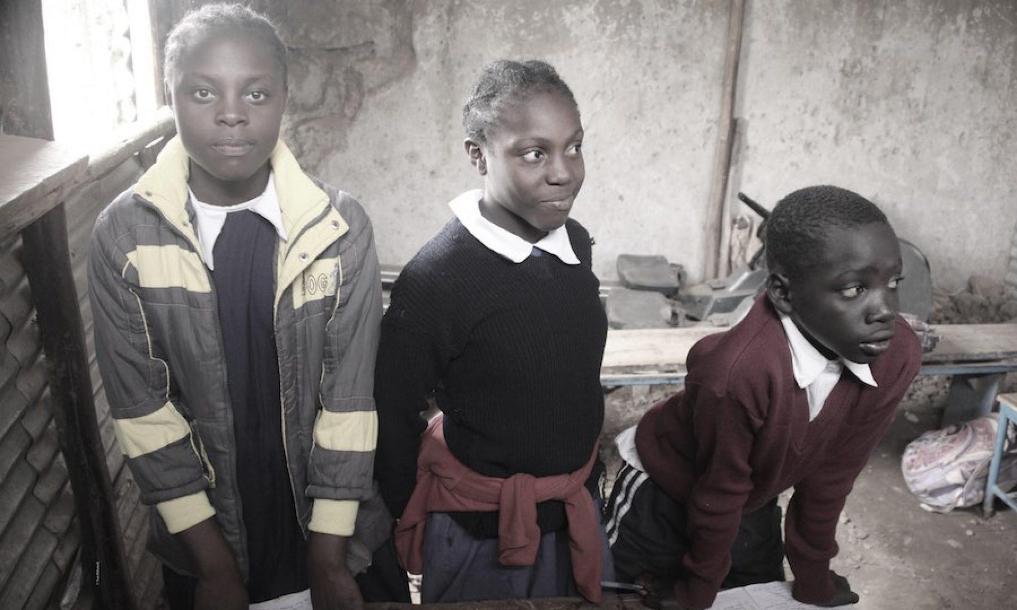 Drei Kinder in einer einfachen Schule im Slum Korogocho. © Tom Rübenach