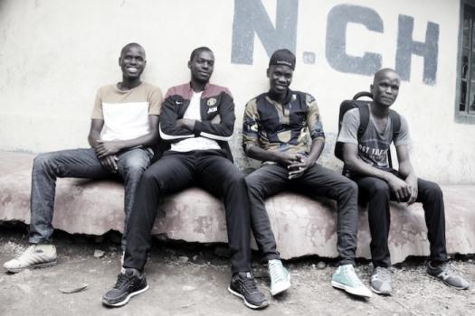 Vier junge schwarze Männer sitzen zusammen, sie gehören zum Team der Ayiera-Initiative. © Tom Rübenach