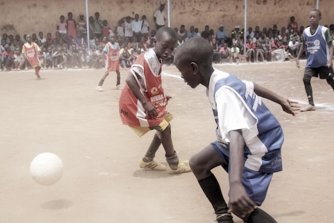 Fußballspielen und Lernen: Das Prinzip der Ayiera-Initiative. - Zwei Jungs kämpfen auf einem Sandplatz um einen Ball. Foto © Tom Rübenach