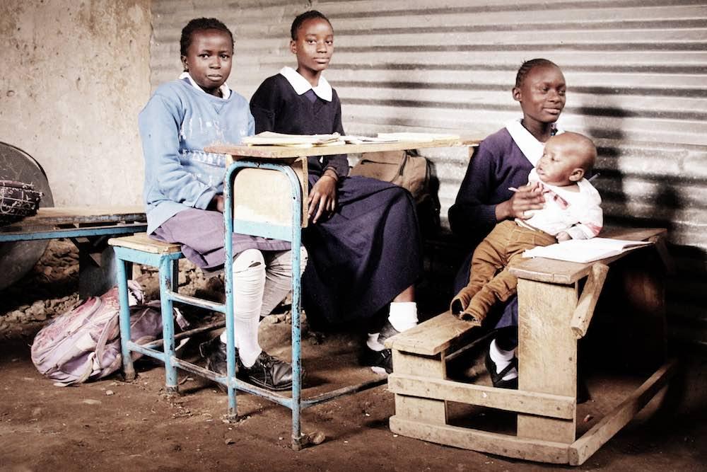 Vier junge Frauen, Mädchen: eine hat ihr Baby auf dem Arm. Sie sitzen in Schulbänken im Slum Korogocho © Tom Rübenach