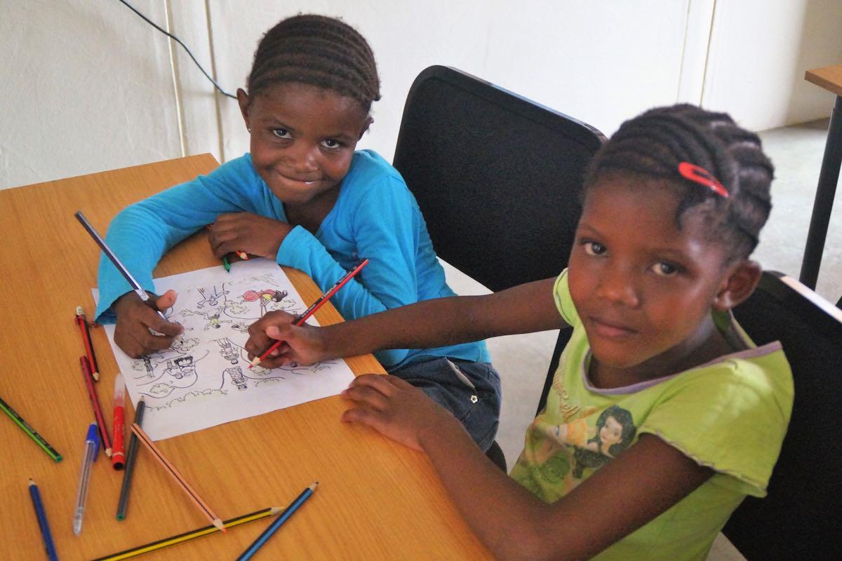 Zwei Mädchen sitzen an einer Schulbank und zeichnen, sehen dabei in die Kamera. © BAS