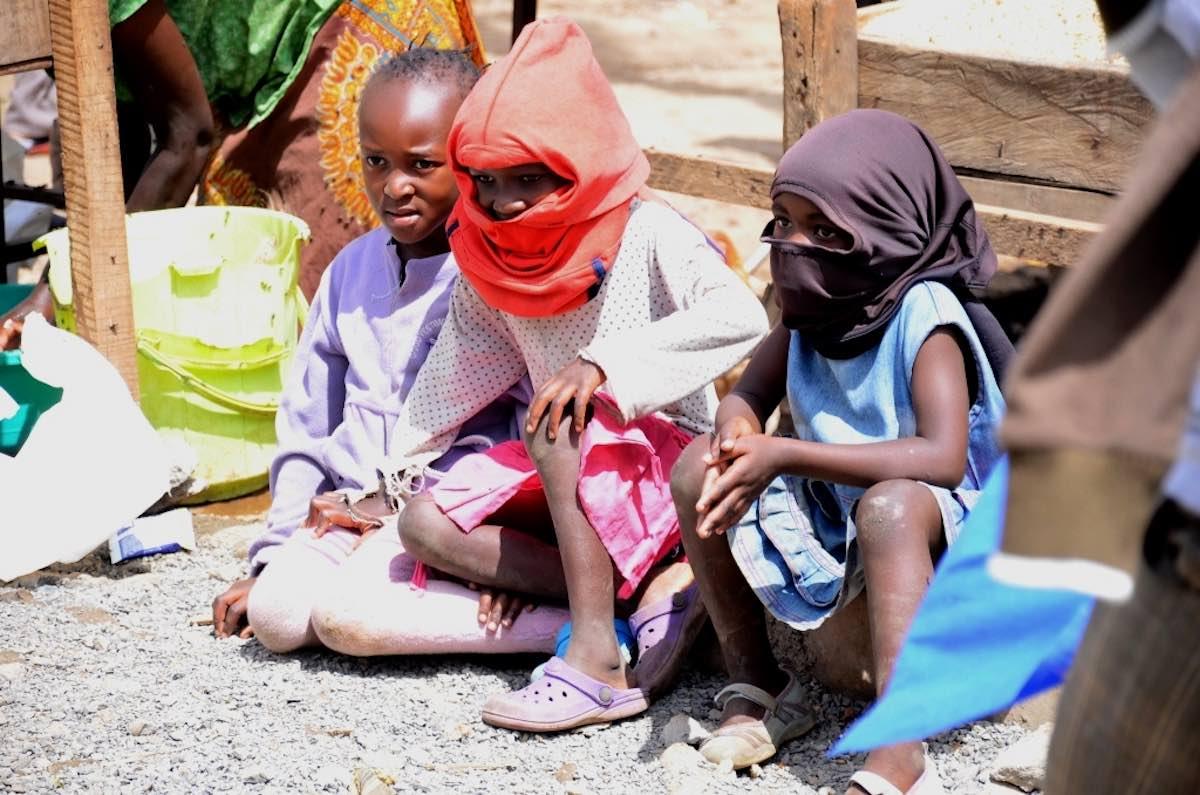 Auch ohne Masken schützen: Kinder ziehen sich Stoff über den kopf. Photo © Lucas Oduor