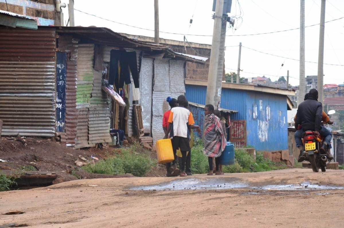Kinder tragen das Wasser von einer Wasserausgabestelle nachhause. Photo © Lucas Oduor