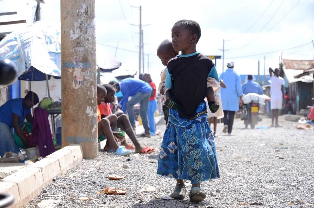 Ein Mädchen im Korogocho-Slum in Nairobi trägt ihre kleine Schwester auf dem Rücken. Photo © Lucas Oduor